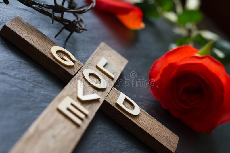 Easter christian wooden cross with an inscription god is love and red rose abstract religion background. Concept royalty free stock photography