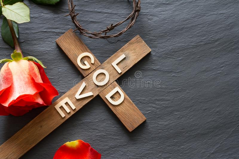 Easter christian wooden cross with an inscription god is love and red rose abstract religion background. Concept stock image