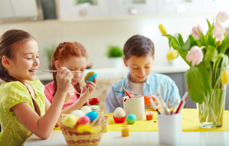 Easter class. Preschoolers decorating Easter eggs at home royalty free stock images