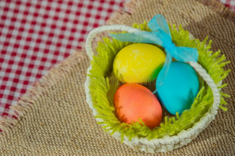 Easter colored eggs in a basket on a canvas napkin and checkered tablecloth stock photography