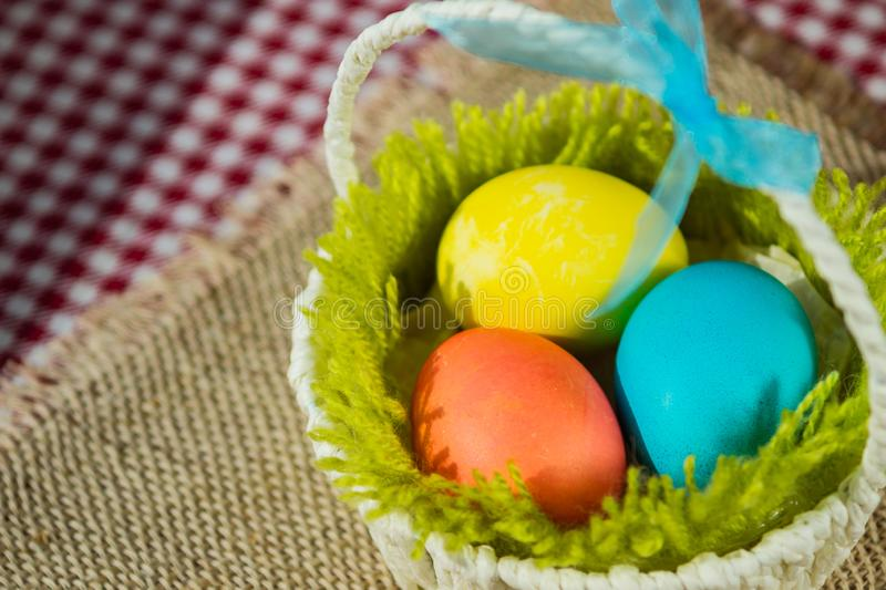 Easter colored eggs in a basket on a canvas napkin and checkered tablecloth royalty free stock photo