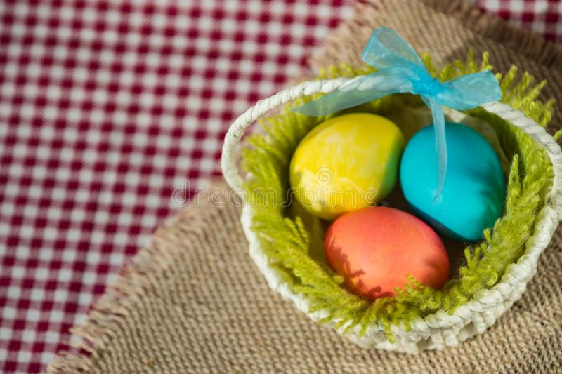 Easter colored eggs in a basket on a canvas napkin and checkered tablecloth stock photos
