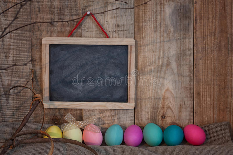Easter colored eggs with bow and black board with copy space for text against natural wooden textured background on linen fabric. royalty free stock images