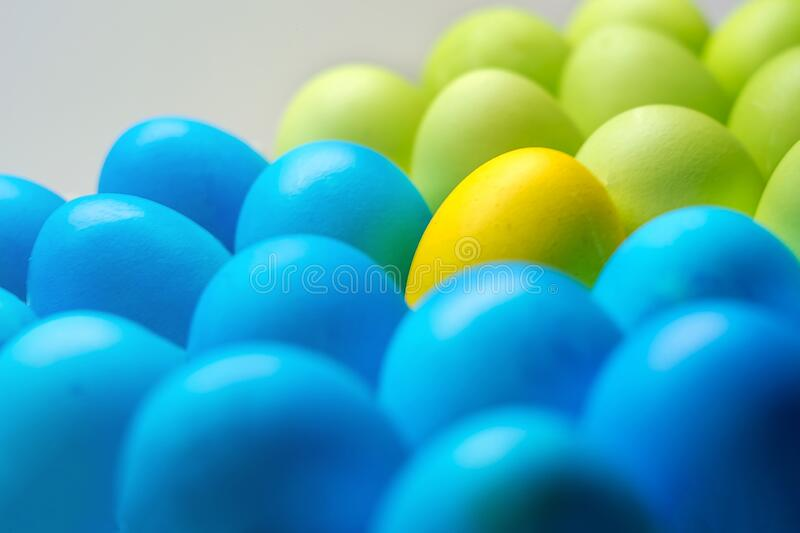 Easter colored eggs multicolor closeup of one of the yellow stands out stock images