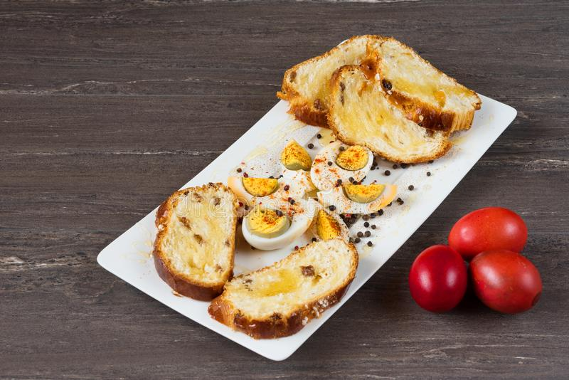 Easter colored eggs and sliced Easter bread in white plate on grey wooden board. royalty free stock photo