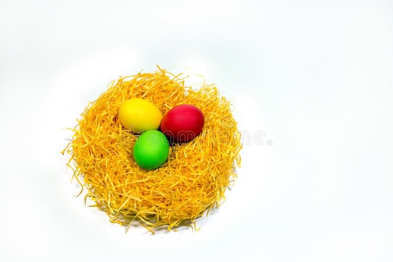 Easter colored eggs in yellow straw nest isolated on white background royalty free stock photos