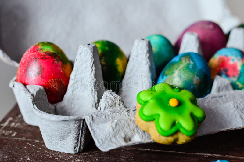 Easter. Colorful easter cookies and hand painted eggs on wooden background royalty free stock image