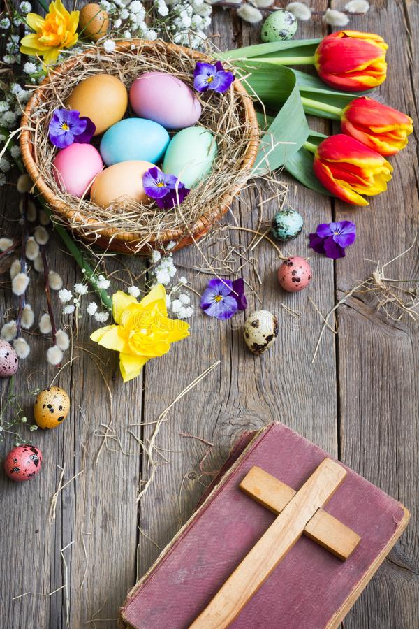 Easter colorful eggs in the nest with flowers on vintage wooden boards with bible and cross. Background royalty free stock photography