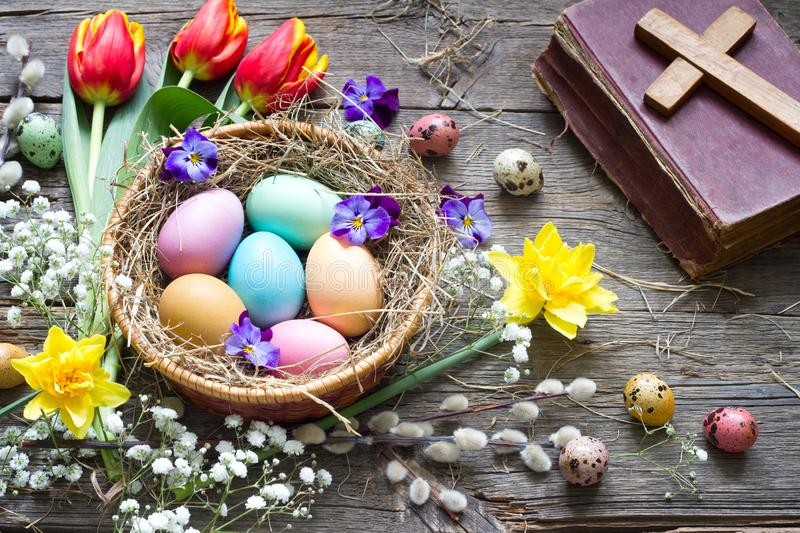 Easter colorful eggs in the nest with flowers on vintage wooden boards with bible and cross. Background stock images