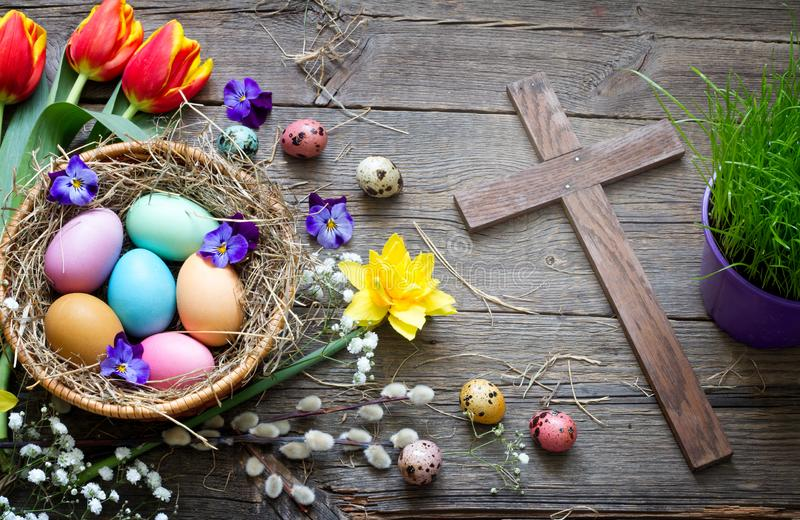Easter colorful eggs in the nest with flowers on vintage wooden boards  and cross royalty free stock photography