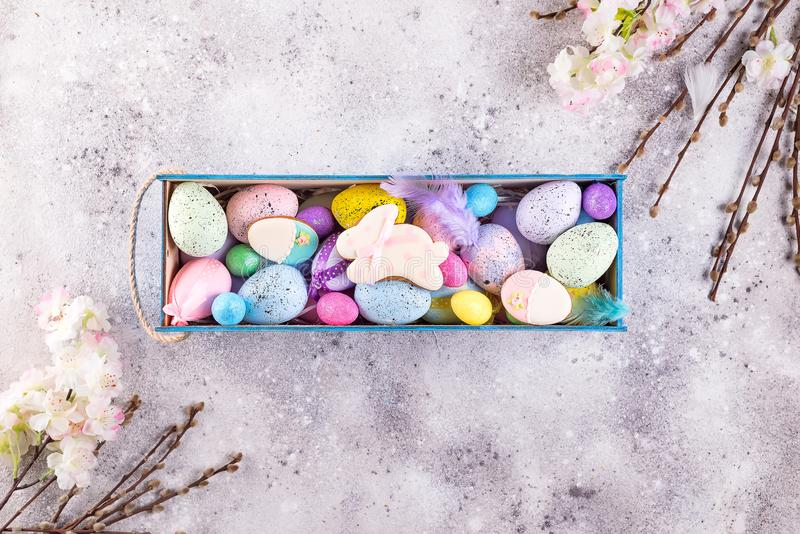 Easter colorful eggs painted in bright colors and glazed cookie bunny with straw nest in wooden box on stone background stock photos