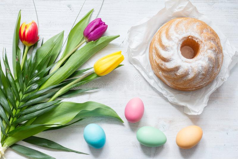 Easter colorful spring tulips with palm and eggs decoration on white wooden natural background. Closeup royalty free stock images