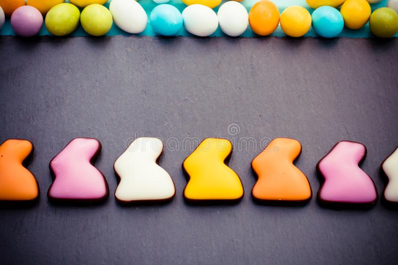 Easter colorful sweet rabbits in a row with small eggs on slate board. Top view. Copyspace. Easter colorful sweet rabbits in a row with small candy eggs on slate royalty free stock photography