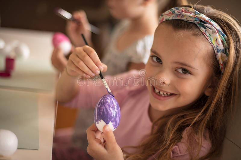 Easter is coming soon. Little girls coloring Easter egg royalty free stock images