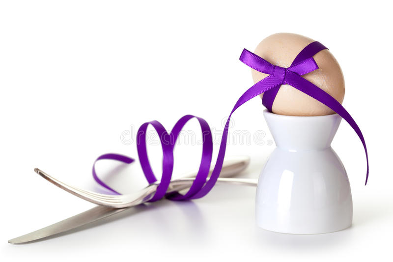 Easter Composition. Easter egg with violet ribbon on white background. Composition with cutlery and egg hand painted a beige paint with glitter royalty free stock photo