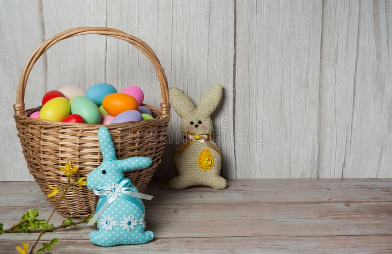 Basket with eggs, funny handmade Easter bunnies and forsythia branches with leaves and yellow flowers on a wooden background. Easter composition. Basket with royalty free stock images