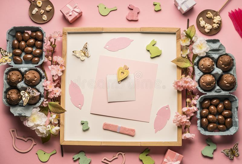 Easter composition with chocolate eggs, spring flowers, various decorations, wooden rabbits and birds on a pink background, space. Easter composition chocolate royalty free stock photography