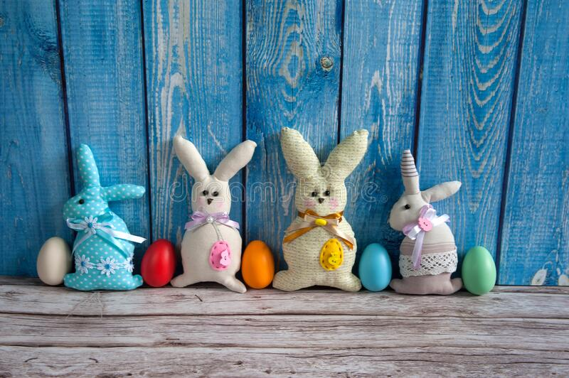 A collection of colorful eggs and funny handmade textile Easter bunnies on a blue wooden background. Easter composition. A collection of colorful eggs and funny royalty free stock images