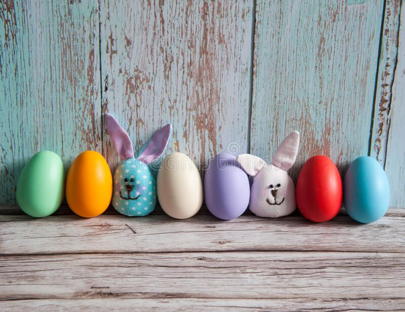 A collection of colorful eggs and funny handmade textile Easter bunnies on a light blue wooden background. Easter composition. A collection of colorful eggs and stock photography