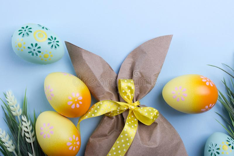 Easter composition with craft paper package in the shape of bunny, colorful easter eggs, and flowers. Top view, copy spa royalty free stock photography