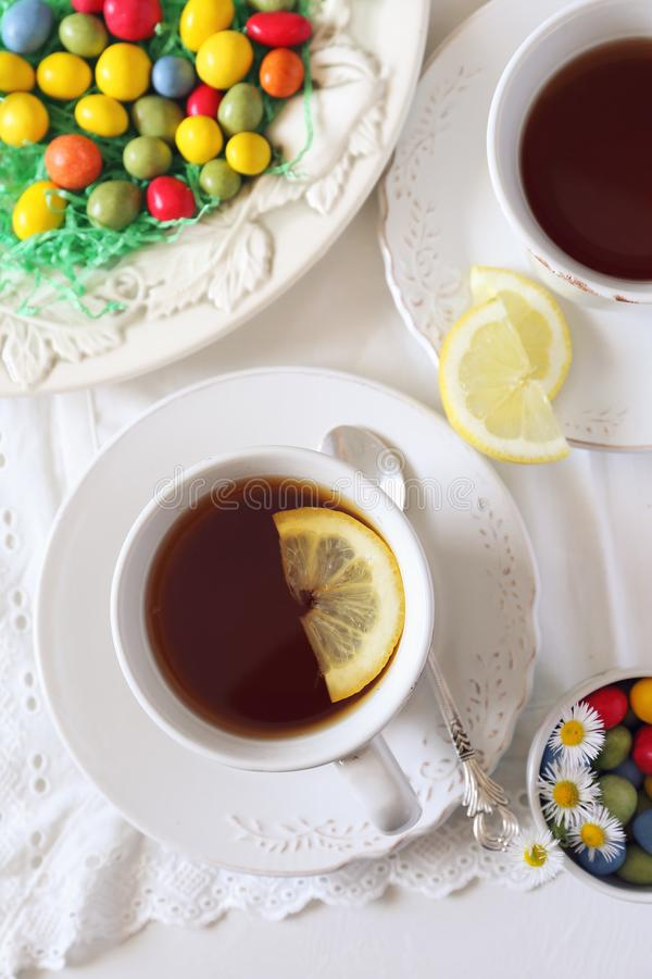 Easter composition: cup of lemon tea drink with colorful candy royalty free stock photos