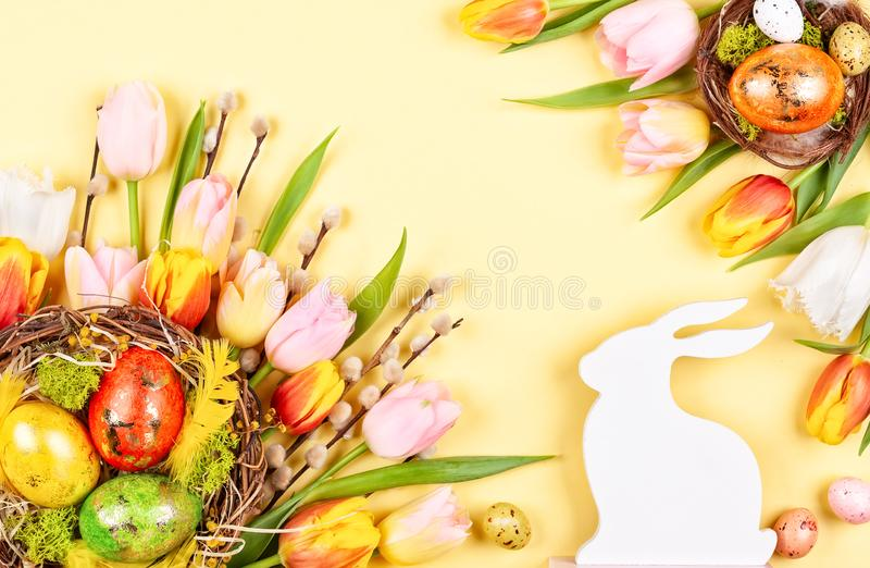 Easter composition with Easter eggs in nest and  spring flowers stock photos
