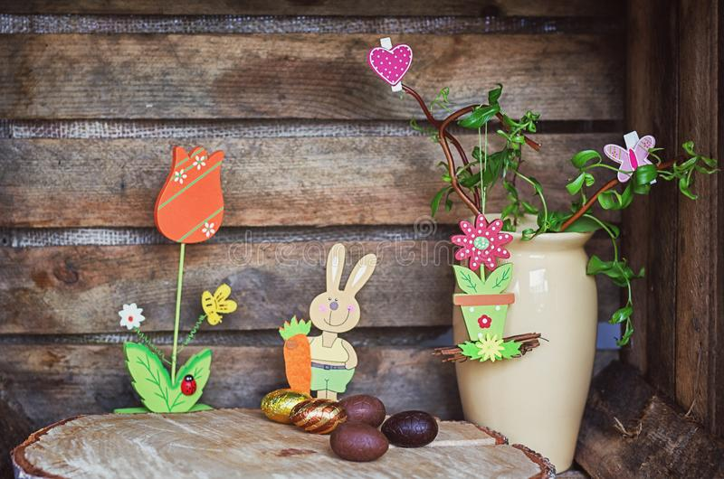Easter composition of Easter eggs, a wriggle hazel with butterfly and heart and an artificial rabbot with carrot and flower with stock photos
