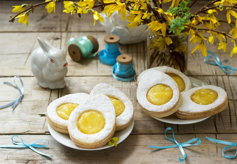 Easter composition with egg-shaped cookies filled with lemon curd, rabbit, bouquet of forsythia and bows royalty free stock photo