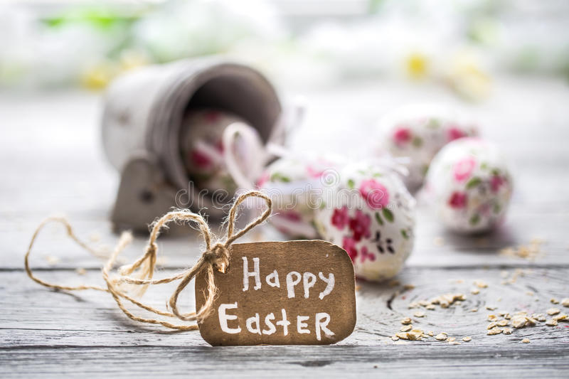 Easter composition with eggs in a bucket. And with the inscription happy Easter is on a light wooden background stock photography
