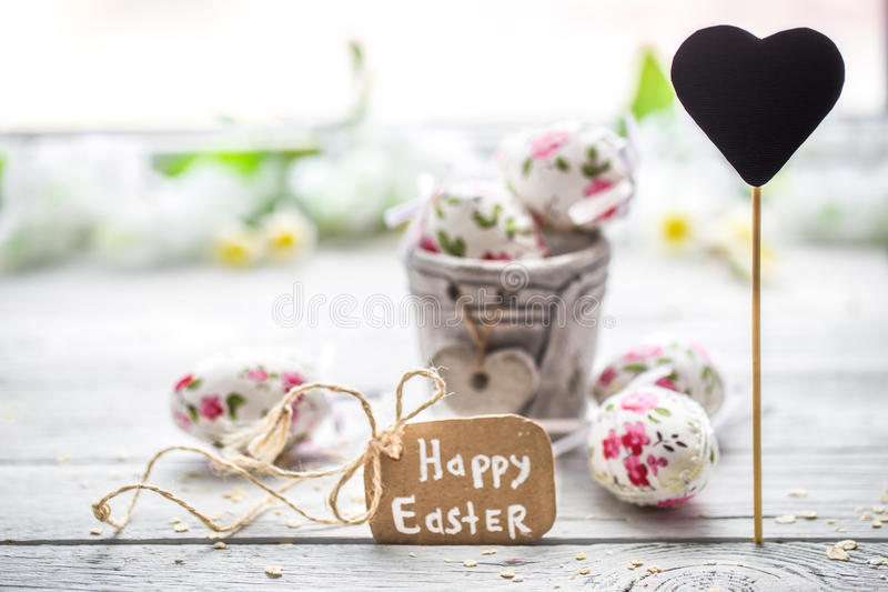 Easter composition with eggs in a bucket. And with the inscription happy Easter is on a light wooden background stock image