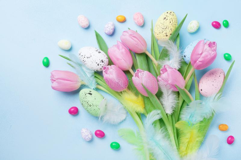 Easter composition with eggs, spring flowers, feathers and colorful candy on blue table top view. stock images