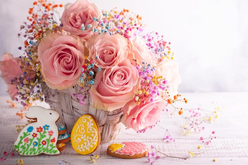 Flower composition with pastel roses and Easter cookies for holiday stock photos