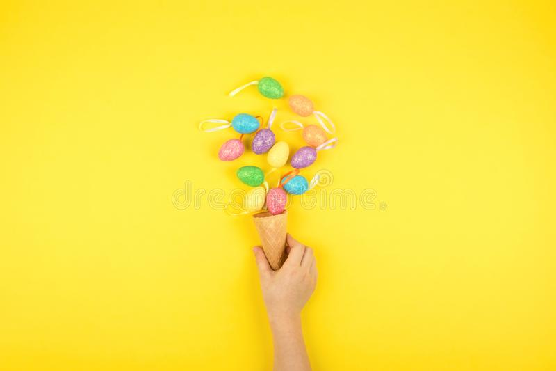 Easter composition, greeting card with child hand, lightbox text Happy Easter, colored decorative eggs on color background stock images