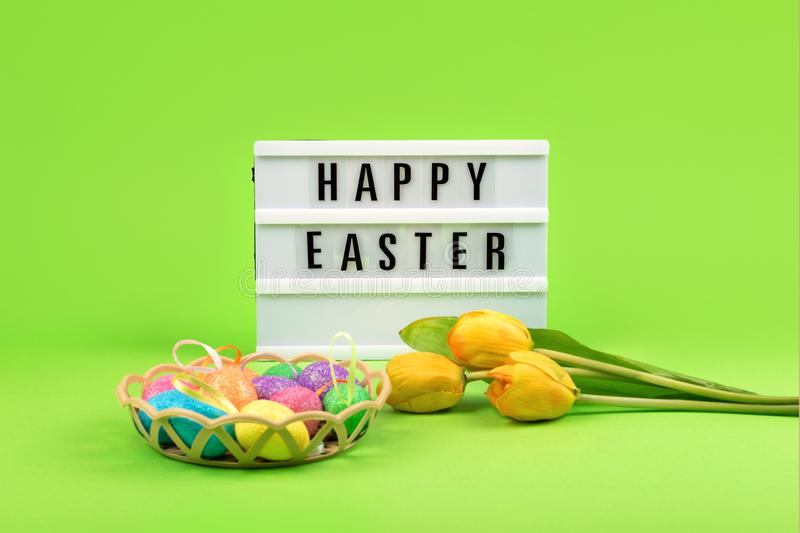 Easter composition, greeting card with lightbox text Happy Easter, colored decorative eggs, yellow tulips on color background royalty free stock photos