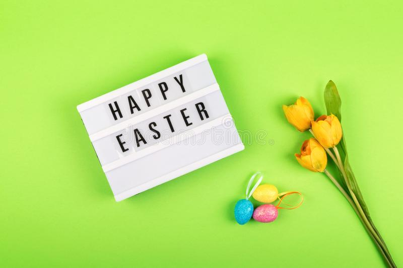 Easter composition, greeting card with lightbox text Happy Easter, colored decorative eggs, yellow tulips on color background royalty free stock photography