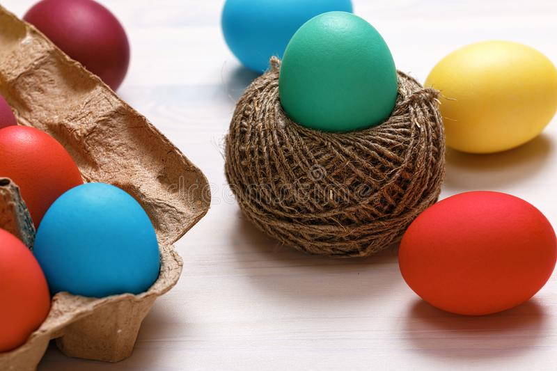 Easter composition. Multi-colored eggs in a box, in a nest of hemp threads, on a white table.  royalty free stock image