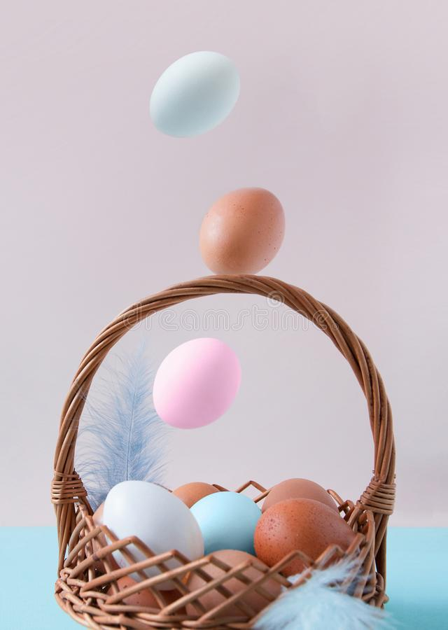 Easter composition. The multi-colored eggs falling in a basket. On a pink-blue background. Happy Easter. stock image