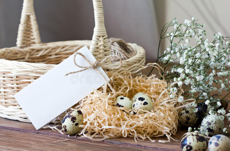 Easter composition with quail eggs, flowers, basket, and place for inscription. Easter eggs in a bowl on a wooden table. Rustic style stock photos