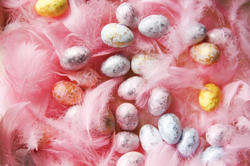 Easter composition with traditional decor of small colored eggs and soft feathers stock images