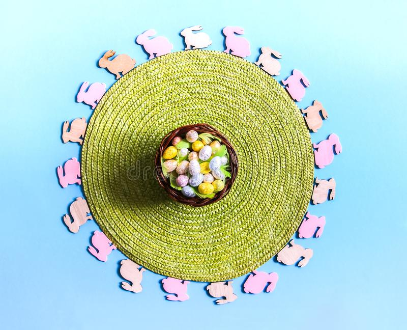 Easter composition with traditional decor. Small decorative colorful wooden rabbit figures and green wicker place mat royalty free stock photography