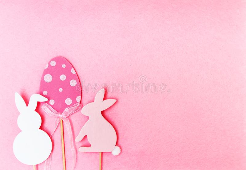 Easter composition with traditional decor. Wooden еgg and rabbit figures on soft light pink background. Easter composition with traditional decor. Wooden stock photography