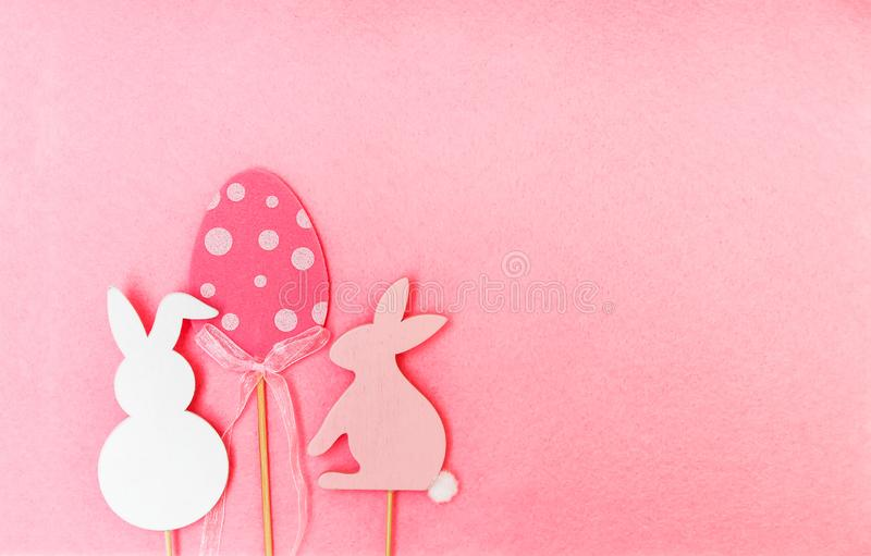 Easter composition with traditional decor. Wooden еgg and rabbit figures on soft light pink background. Easter composition with traditional decor. Wooden royalty free stock photography