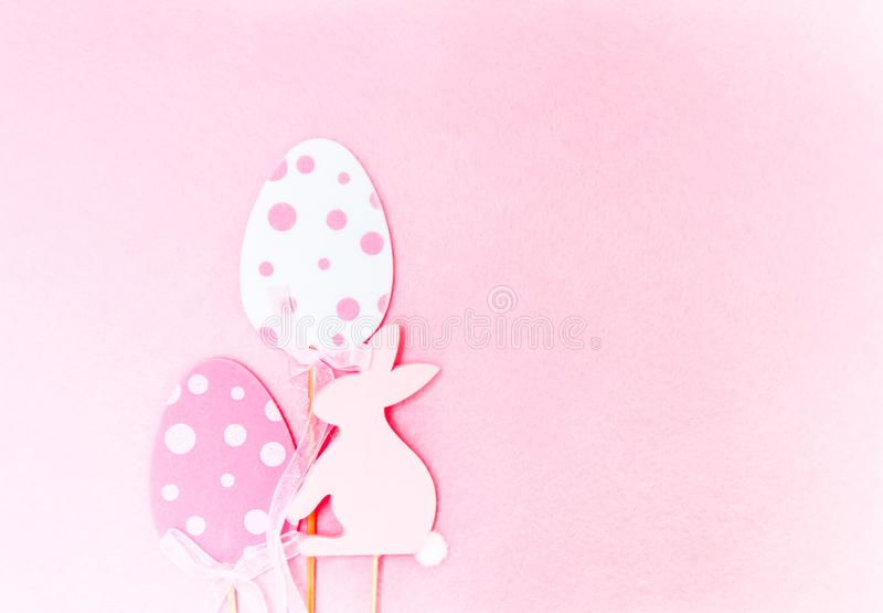 Easter composition with traditional decor. Wooden еgg and rabbit figures on soft light pink background. Easter composition with traditional decor. Wooden stock photo