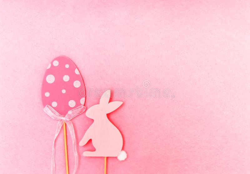Easter composition with traditional decor. Wooden egg and rabbit figures on soft light pink background. Easter composition with traditional decor. Wooden royalty free stock photo