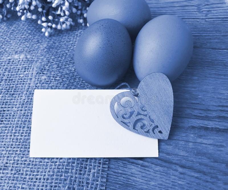 Easter composition on wooden background.  Eggs, empty card with decor heart on sackcloth. Toned  blue image. stock images
