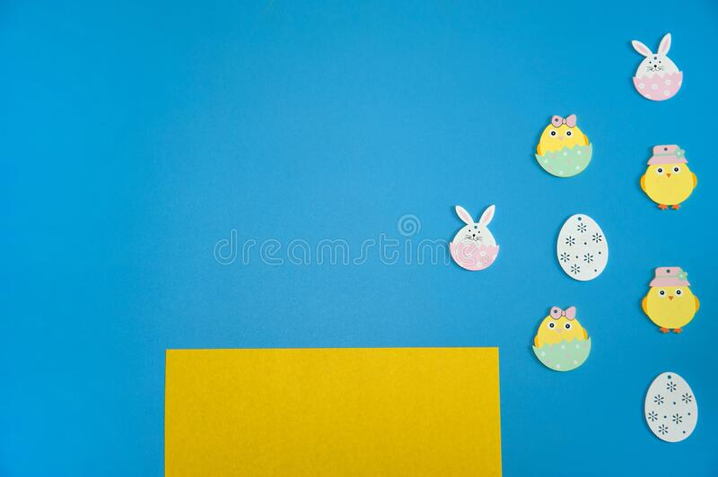 Yellow paper blank and cute decorative Easter symbols on a light blue background. Easter composition. Yellow paper blank and cute decorative Easter symbols on a royalty free stock photos