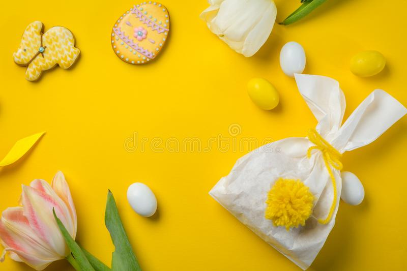 Easter concept - bunny shaped bag with eggs and flowers on bright yellow background,. Top view royalty free stock photography