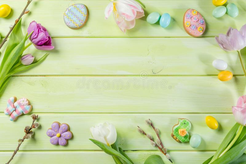 Easter concept - cookies with flowers on green wood background. Copy space royalty free stock photography