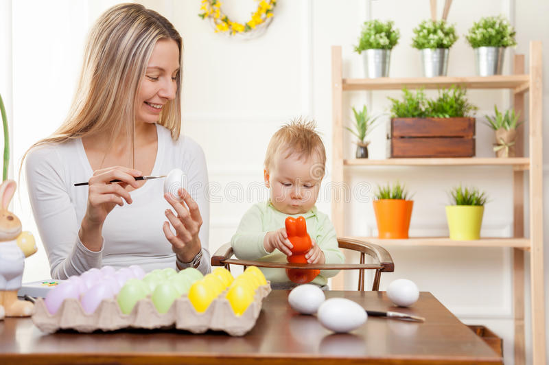 Easter concept. Happy mother and her cute child getting ready for Easter royalty free stock image