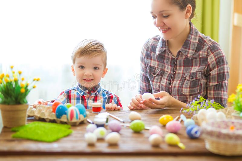 Easter concept. Happy mother and her cute child getting ready for Easter by painting the eggs stock photo